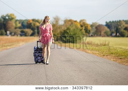 Young Woman Hitch-hiking On A Road With Luggage Bag At The Fields