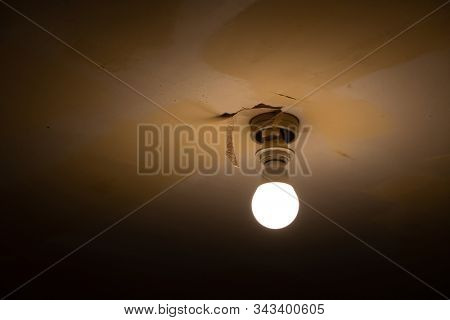A bare light bulb on a ceiling of a old house or a house during renovation.