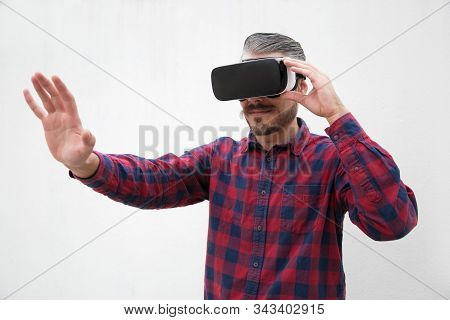 Concentrated Man Using Virtual Reality Headset. Focused Bearded Man In Checkered Shirt Moving Hand A