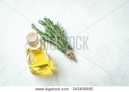 Bunch Of Fresh Rosemary And Garlic And Bottle With Olive Oil On A Light Background.top View With Cop