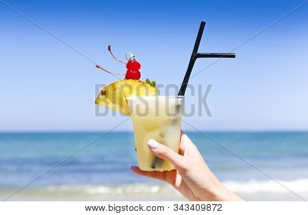Tropical Pina Colada Drink With Pineapple In A Hand Of The Woman On A Tropical Beach With Ocean In T
