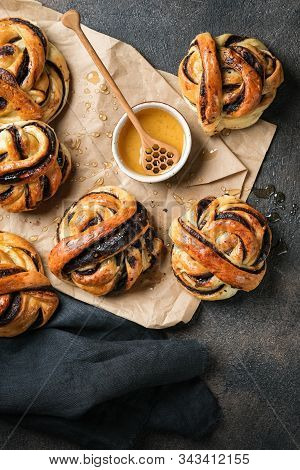 Homemade Buns With Dark Chocolate In A Creamic Plate With Honey On A Light Wooden Background.