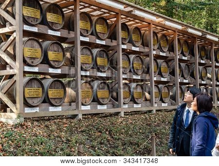 Unidentified People  Looking At Traditional Sake Barrels Wrapped In Straw By Meiji Shrine