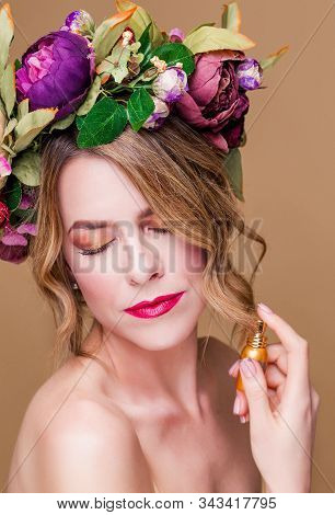 Close-up Portrait Of Young Woman In Floral Wreath Spraying Perfume Isolated On Ocher Background