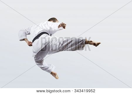 On A Light Background, An Adult Athlete With A Black Belt Beats A Kick In Jump
