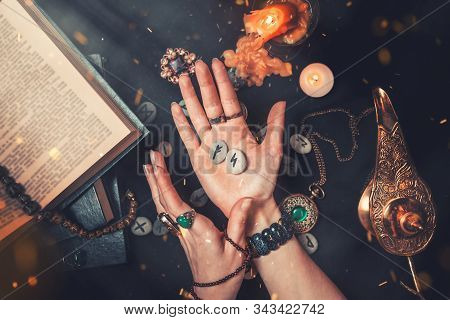 Astrology And Esotericism. The Witch Is Holding In His Hands The Rune Stones. Hands Close Up. On A B