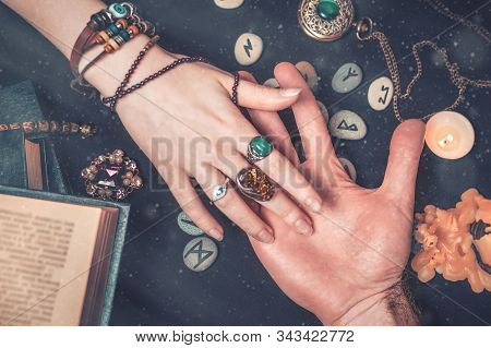Astrology And Esotericism. A Fortune Teller Reads A Mans Palm. On A Black Background Lie Runes, A Ca