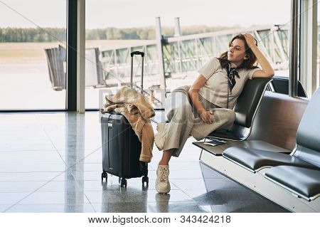 Airport Travel Lifestyle. Young Gen Z Girl Traveler Sitting In Terminal Hall With Her Luggage, Troll