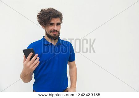 Positive Guy With Smartphone Looking At Camera With Smirk. Handsome Bearded Young Man In Blue Casual