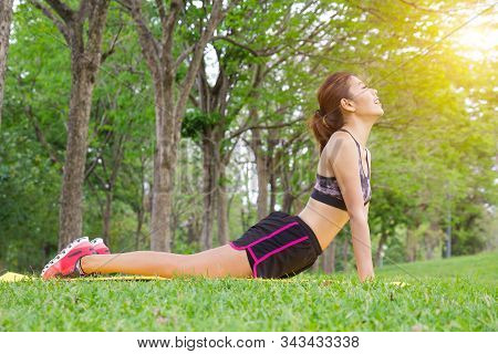 Young Asian Woman Pose Practicing Yoga In Beautiful Nature. Meditation In Morning Sunny Day In Green