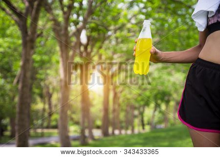 Female Runner Standing In Park Outdoors Holding Mineral Water Bottle, Close Up. Fitness Athlete Woma