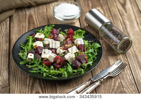 Salad With Beetroot, Feta Cheese, Arugula And Spicy Dressing On A Rustic Background. Healthy Food. T