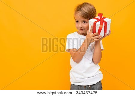 Holiday Concept. Attractive Boy With Gift Box On Bright Yellow Background.