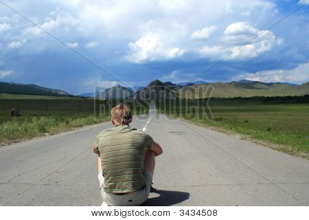 Person Sits On Road