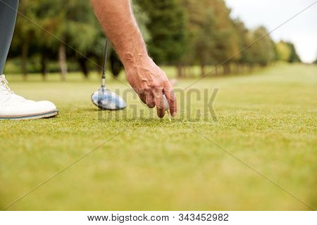 Close Up Of Mature Male Golfer Preparing To Hit Tee Shot Along Fairway With Driver