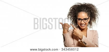 Positive Woman surprise showing product. Attractive young female with Afro presenting product. Girl points aside with cheerful expression. African American Model shows something amazing at blank space
