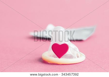 A Simple Flat Lay About Safe Sex: An Open Condom, A Small Heart, In The Background A Silver Packagin