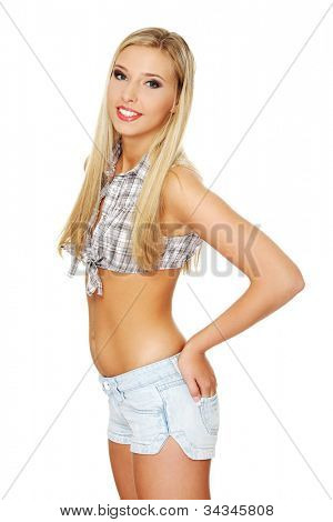 Young, attractive woman with hands in back pockets of jeans shorts. Pretty long-hair blond girl wearing short pants and short, plaid shirt smiling. Isolated on the white background.