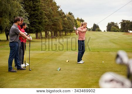 Two Couples Golfing Hitting Tee Shot Along Fairway With Driver With Clubs In Foreground