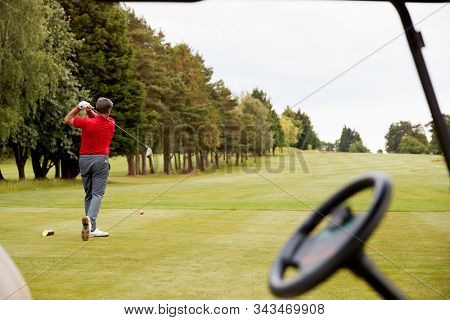 Mature Male Golfer Hitting Tee Shot Along Fairway With Driver Viewed Through Buggy Window