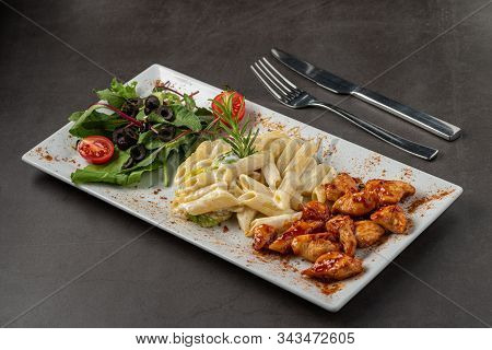 Grilled Cubed Chicken Served With Pasta And Salad On White Plate On Dark Stone Table