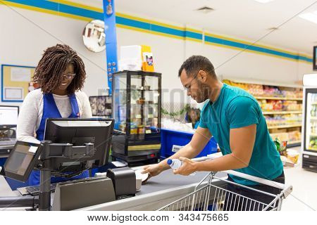 Female Cashier Reading Barcodes At Cash Register. Male Customer In Casual Putting Products From Cart
