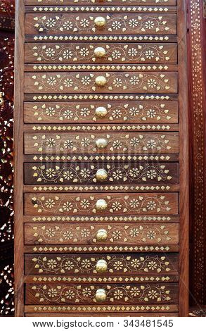 Indian Wooden Cabinet With Drawers With Golden Inlay And Round Handles, Vertical Oriental Background