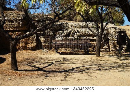A Bench In Front Of Which Shadows From The Trees, Against The Background Of An Ancient Wall. The Val