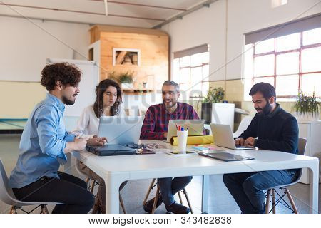 Creative Group Working On Startup, Using Laptops In Modern Co-working With Potted Plant. Business Co