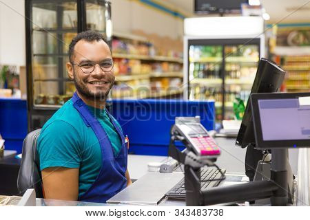 Smiling African American Cashier Sitting At Checkout. Cheerful Bearded Young Man In Eyeglasses At Wo