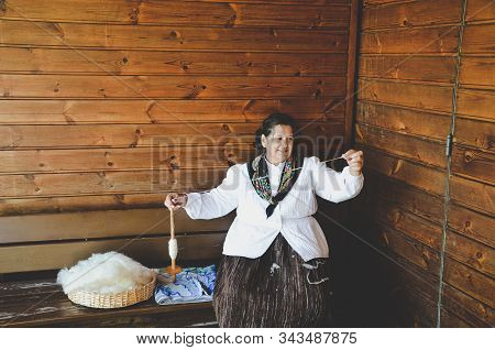 Santana, Madeira, Portugal - Sep 24, 2019: Woman In Traditional Costume Sitting On A Wooden Bench An
