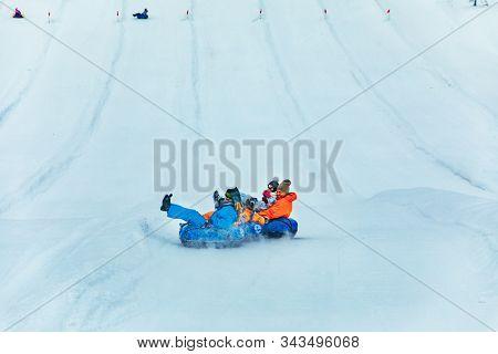 Lviv, Ukraine - January 7, 2019: People Having Fun. Snow Tubing Down By Winter Hill