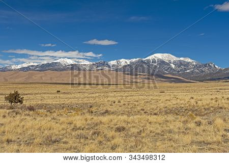 Looking Across The Plains At Sand Dunes And Snowy Mountains In Great Sand Dunes National Park In Col
