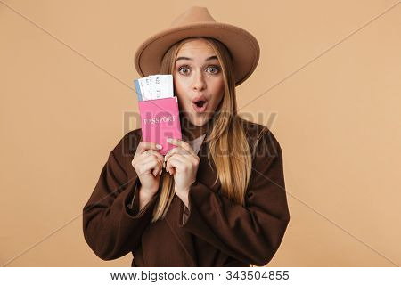 Image of young optimistic girl wearing hat holding passport and travel tickets isolated over beige background