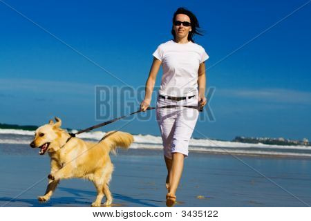 Young woman running on the beach with dog poster