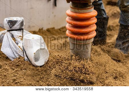 Close Up Details Of A Man Operating Rammer, Aka A Tamper, At Work On A Construction Site, Compacting