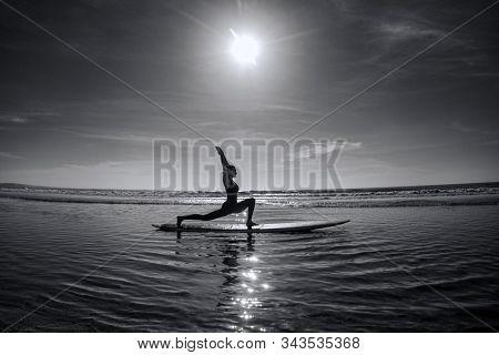 A woman performing a yoga asana Virabhadrasana - warrior pose on a longboard in the sea