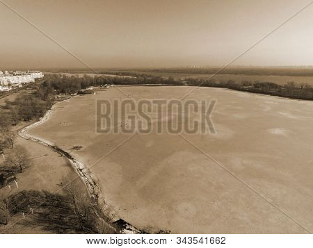 Frozen bay of Dnepr river in residential area of Kiev at winter time (drone image) .Many fishers on ice. Danger hobby. End of winter.  Kiev,Ukraine