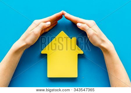 Property Insurance Concept. Hand Defends House Cutout On Blue Backgound Top View