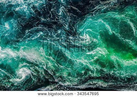Abstract background. Waves of water of the river and the sea meet each other during high tide and low tide. Whirlpools of the maelstrom of Saltstraumen, Nordland, Norway