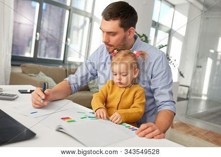 multi-tasking, freelance and fatherhood concept - working father with baby daughter at home office