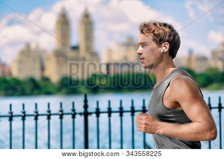 Wireless earbuds man running in Central Park New York city listening to music with wearable technology bluetooth earphone device.