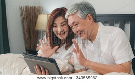 Asian Senior Couple Using Tablet At Home. Asian Senior Chinese Grandparents, Video Call Talking With