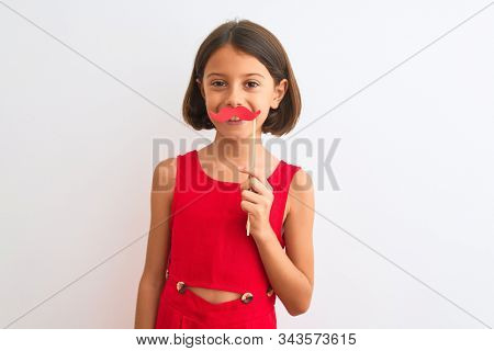 Beautiful child girl holding fanny party mustache standing over isolated white background with a happy face standing and smiling with a confident smile showing teeth