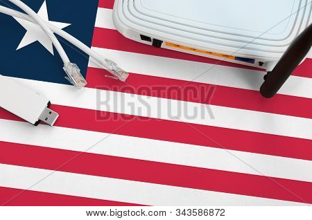 Liberia Flag Depicted On Table With Internet Rj45 Cable, Wireless Usb Wifi Adapter And Router. Inter
