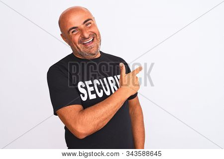 Middle age safeguard man wearing security uniform standing over isolated white background cheerful with a smile of face pointing with hand and finger up to the side with happy and natural expression