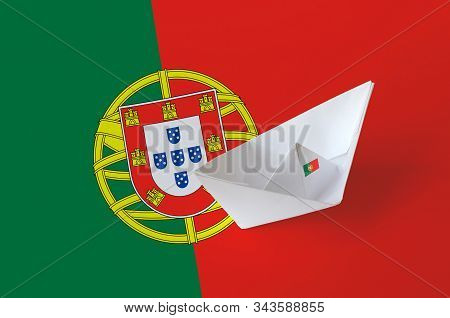 Portugal flag depicted on paper origami ship closeup. Handmade arts concept poster
