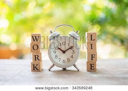 Vintage White Alarm Clock With Wood Word Work And Life Using As Background Business Concept And Bala