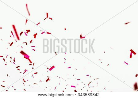 Confetti Explodes On A White Background. Festive Salute Of Shiny Red Paper. Background Decoration Fo