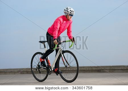 Young Woman Cyclist Riding Road Bike on the Free Road at Cold Autumn Day. Healthy Lifestyle and Urban Sport Concept.